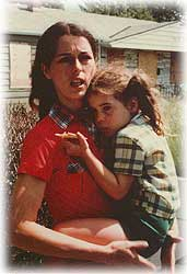 Gibbs, looking distraught, holds her daughter, with boarded-up houses