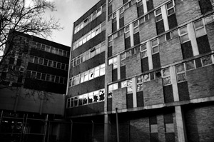 Black and white photo of a building with many windows, some broken, security fences at the bottom