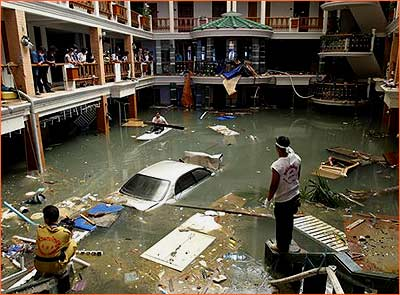 Hotel lobby flooded, car floats among debris