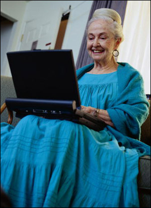 Elderly woman in blue dress smiling and sitting with laptop computer on her lap.