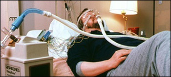 Man monitored by wires lying on bed in a lab wearing mask with tubing leading to a machine