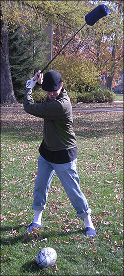 Man wearing slippers outside takes golf swing at a football on a tee