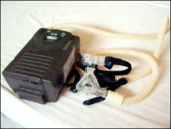 A black box with tubing that leads to a black attachment used to strap on face for breathing