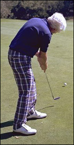 Man with plaid pants putts a golf ball across the green on a golf course