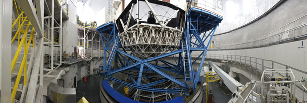 Inside view of large domed structure with blue and white steel beams supporting telescopes