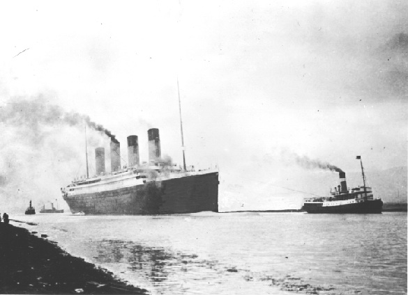 Black and white photo of massive ship on water with smoke coming from 4 stacks, smaller ship nearby.
