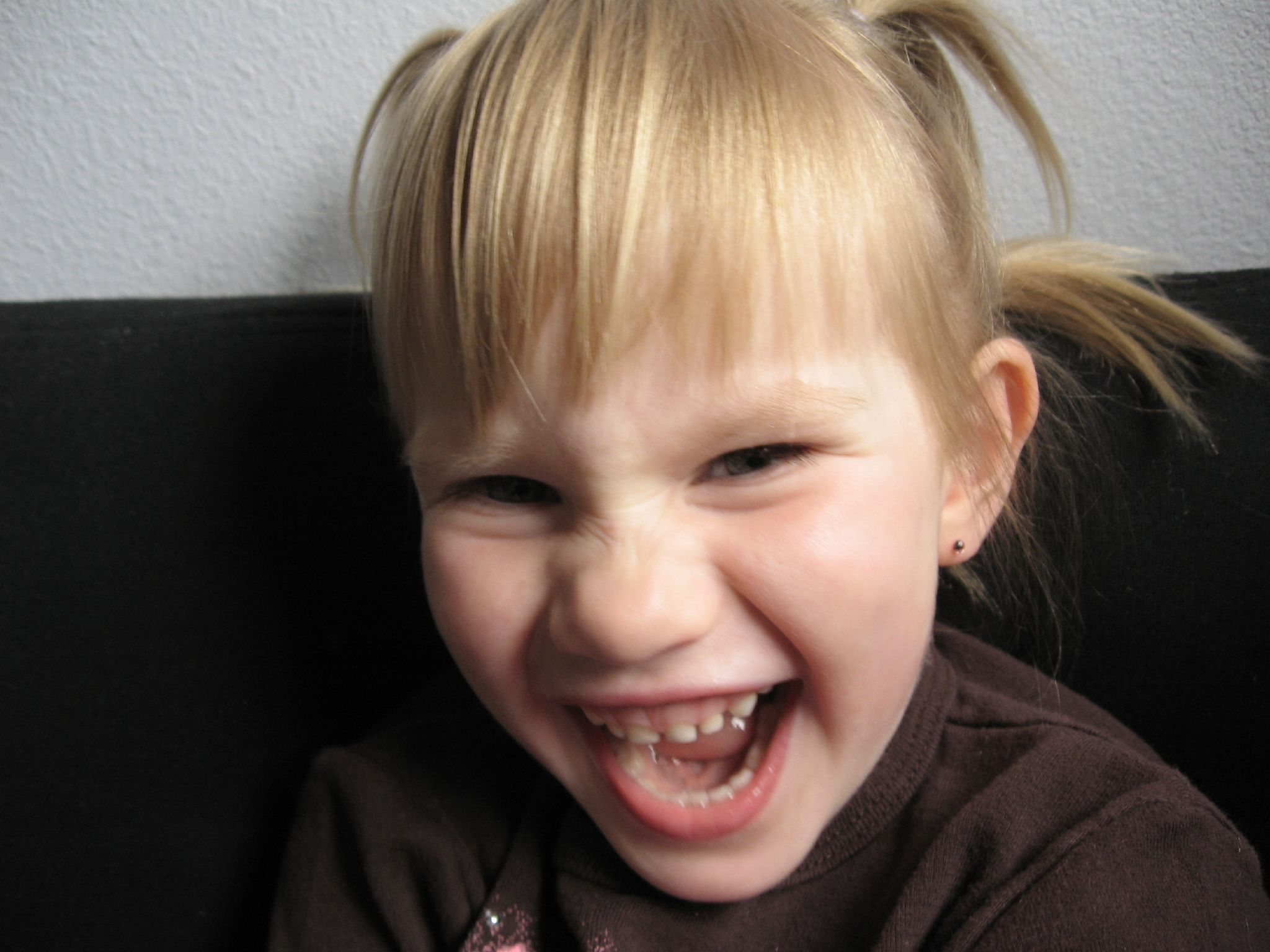 Blond-haired girl, mouth wide, grins at camera, her eyes almost closed, upper teeth showing.