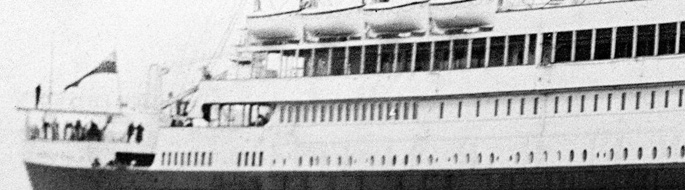 black and white photo, detail of ship bow with people on deck, lifeboats above attached to ship