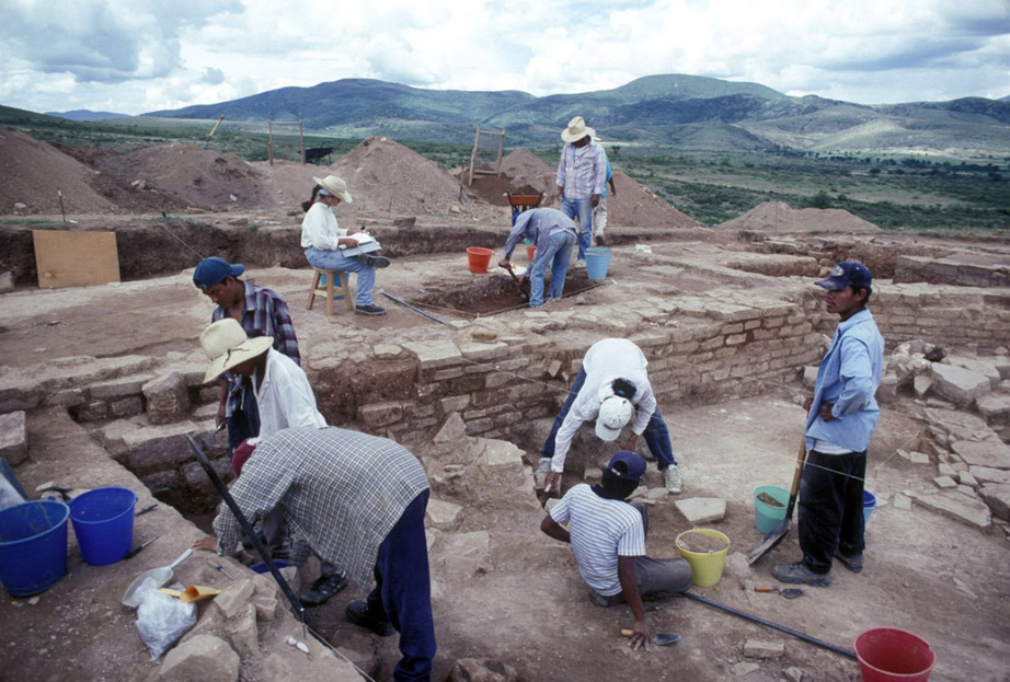 Excavation site, two people working, brown dirt on ground, low stone walls in squared sections