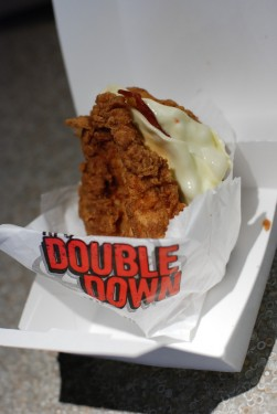 A sandwich with fried chicken on outside, white cheese in a paper wrapper, set on a table.