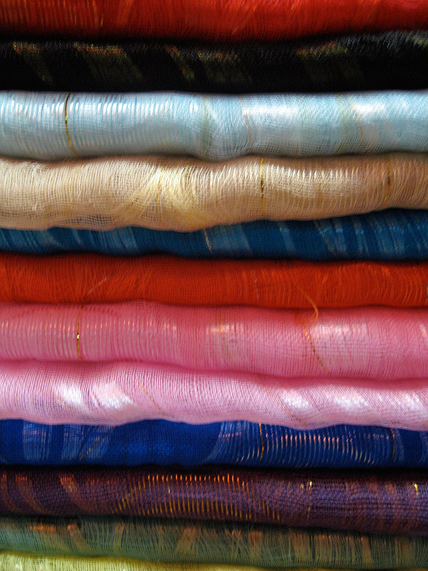 A pile of folded pieces of silk fabric in many bright colors