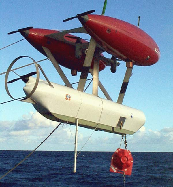 White tube-like machine with propeller, two red rocket-like top attachement, suspended over ocean.