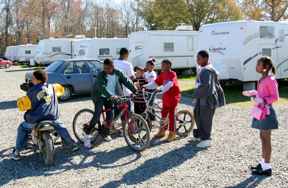 ight African American kids, three on bikes, playing in front of row of six new trailers and two cars