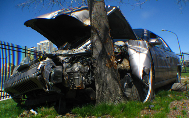 Silver sedan crashed head-on into tree in an urban setting
