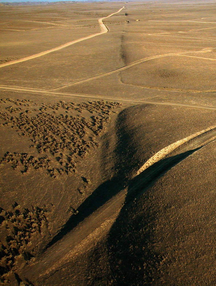 Expansive desert with dirt roads cut through a long gully at the center, marking the fault.