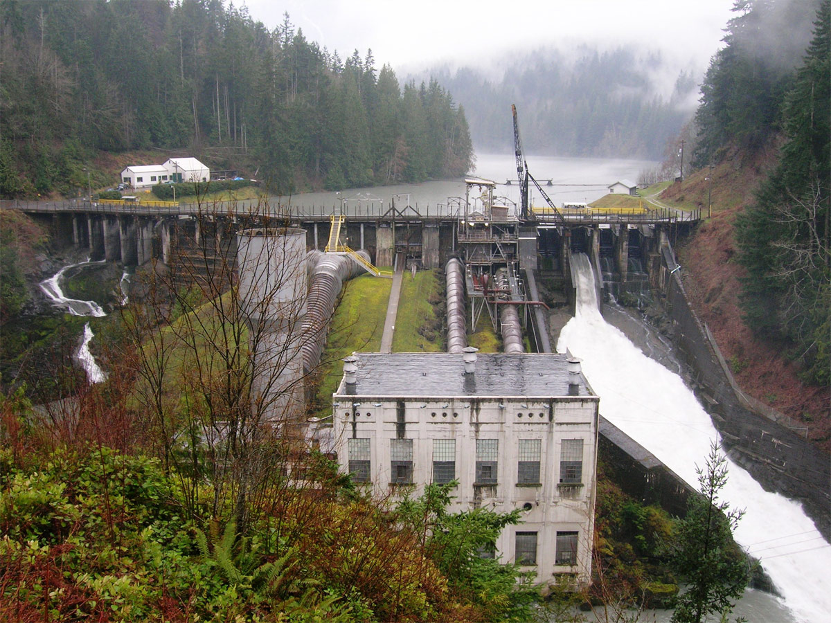 concrete dam blocking tree-lined river, white two-story building in foreground partly hidden by plants