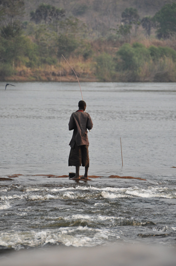 Man fishes with a stick, standing on rocks as river trickles past his feet