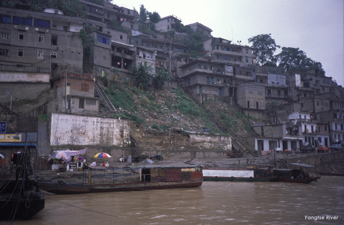 A few long flat boats sit in brown river; steep river bank covered in cascading, cinder block apartments.