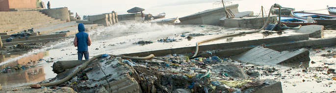 trash litters water and bank of the Ganges River