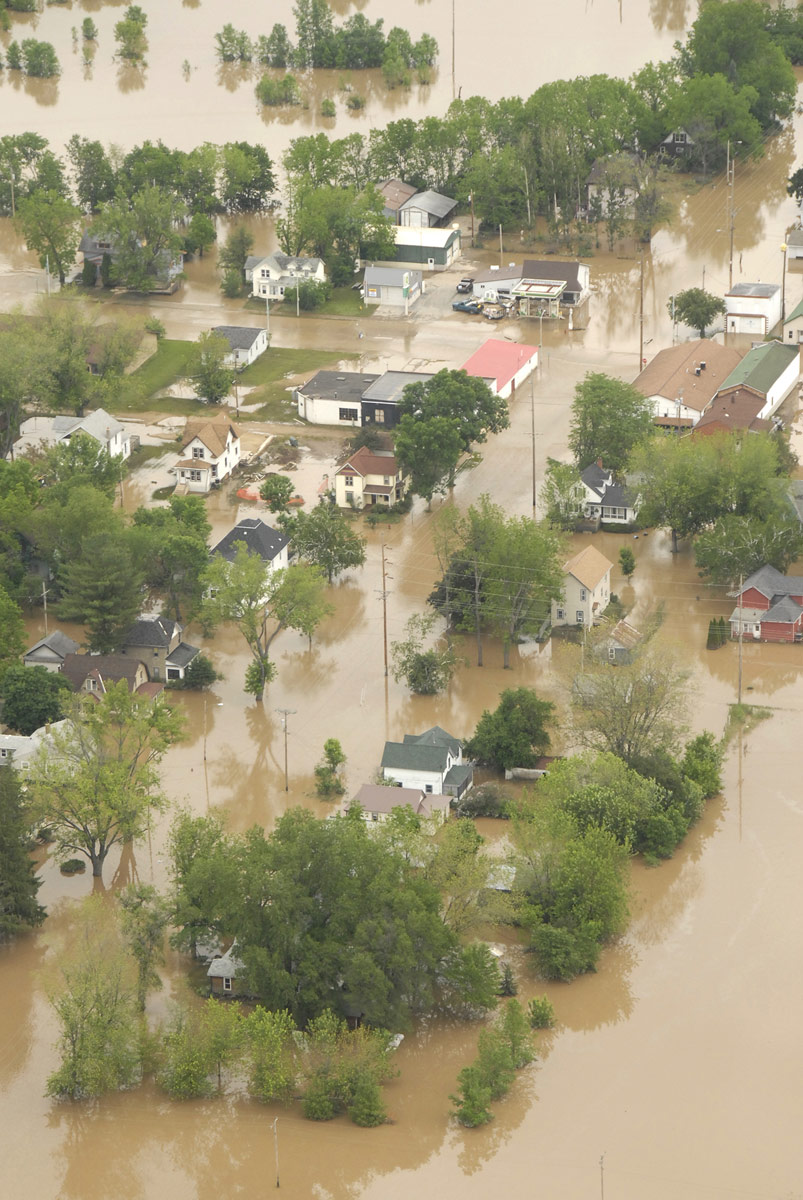 Several dozen houses on tree-lined streets are submerged in muddy water