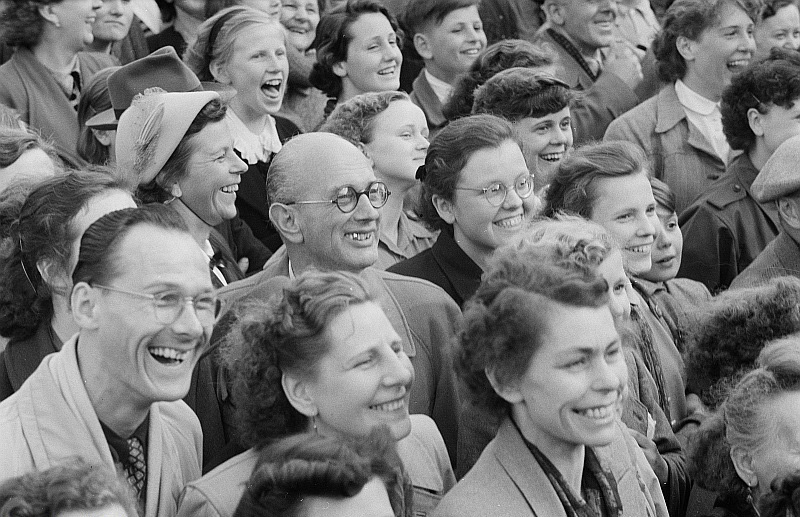 Black and white photo of a couple dozen men and women smiling, facing same direction
