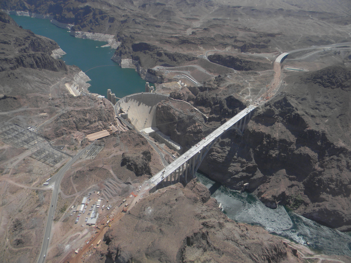 Arid canyon filled by blue river with huge dam and bridge with traffic crossing it