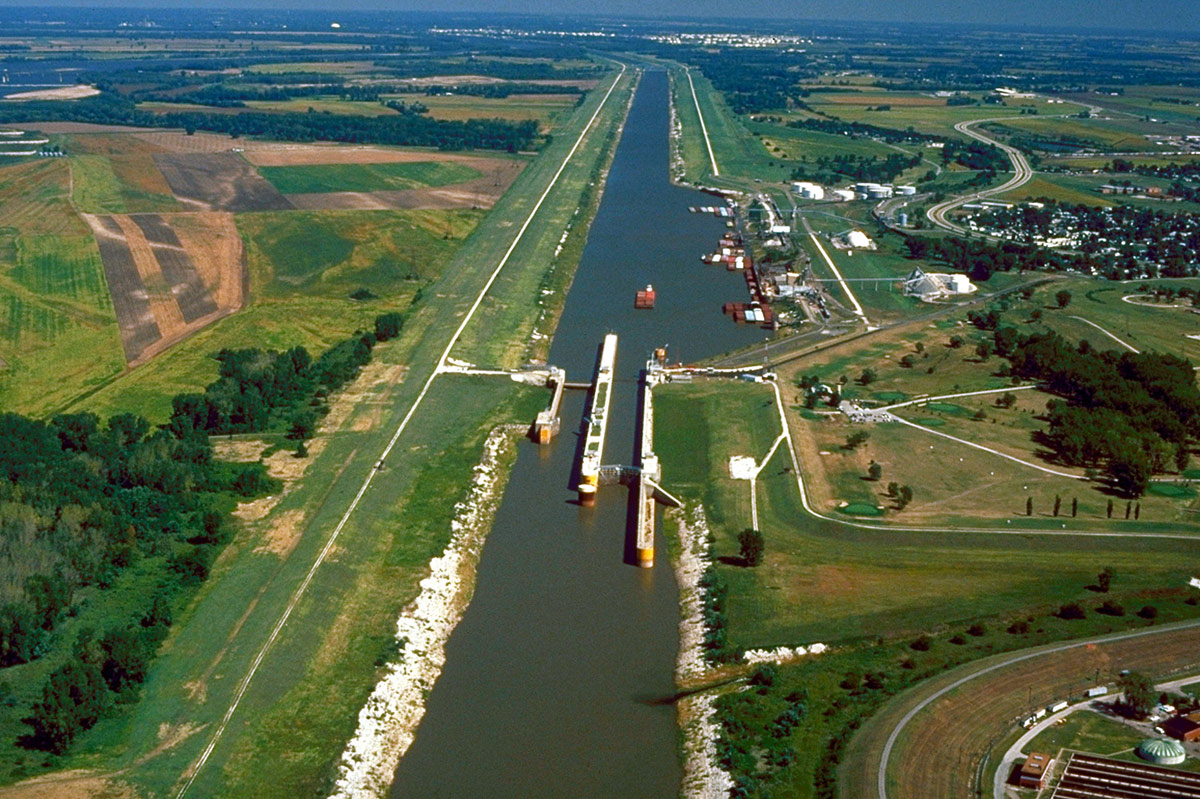 Aerial view of river with lock near industrial site, river banks very straight and lined with rocks