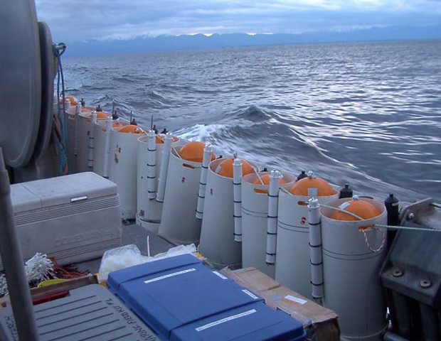 Eleven buoys with round orange tops line side of ship deck, rough sea waters in background