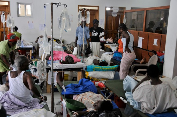 Small crowded hospital room with 3 rows of Haitian patients with intravenous lines on cots, 4 non-patients standing