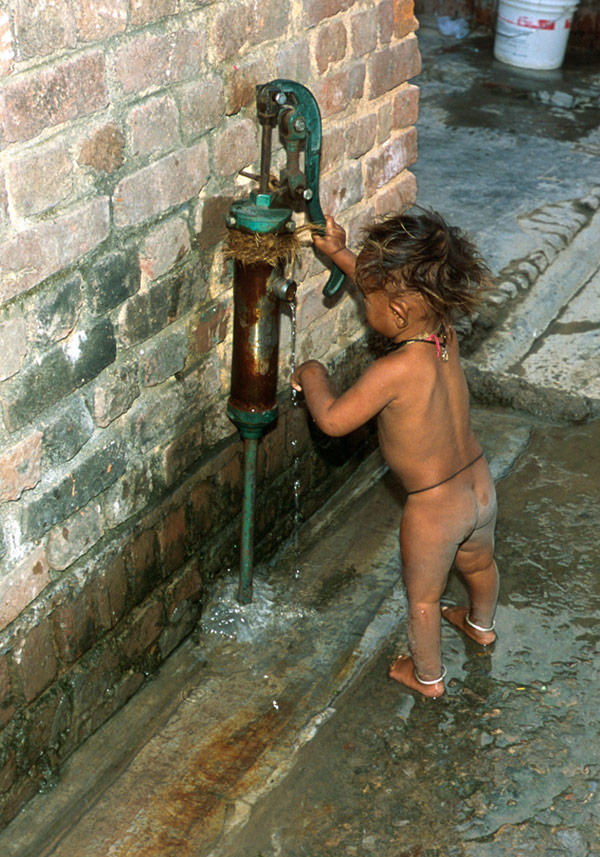 Naked Indian toddler pumping water and washing hand at pump attached to brick building