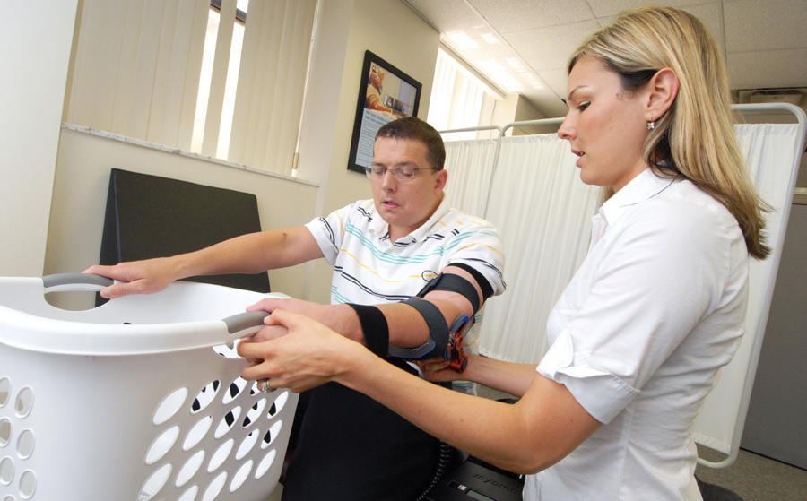 Female doctor helping male stroke patient wearing a robotic arm brace to lift a laundry basket