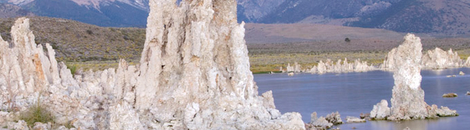 white, stalagmite-looking rock formations rise out of blue lake, mountains in background