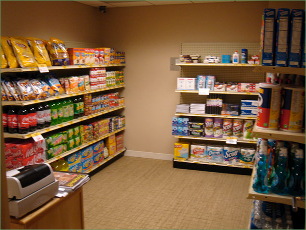 Three walls of store shelves packed with food and household items, cash register in front left corner