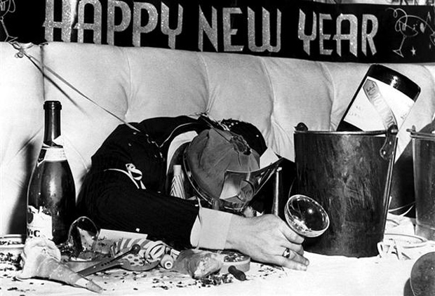 Man wearing party hat and holding drink glass, his head resting on a table littered with bottles and party favors