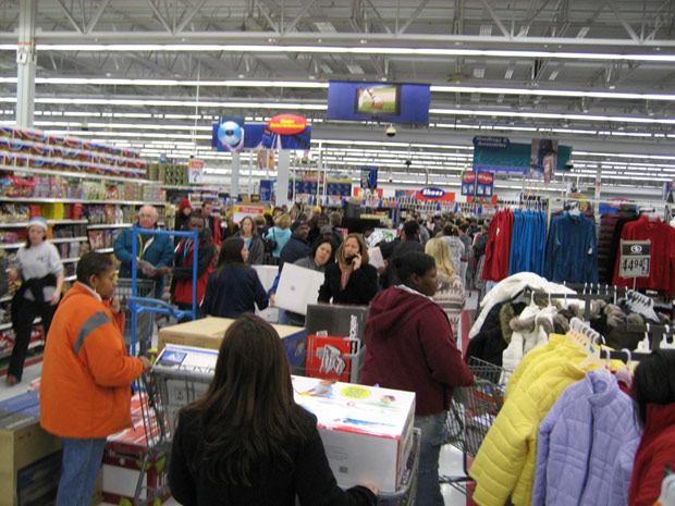 Crowd of people in store isles with carts filled with boxes, well-stocked shelves and racks scattered about