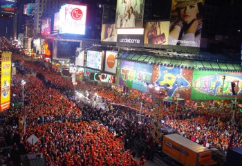Crowd wears red hats in Times Square, huge electronic displays light the scene.