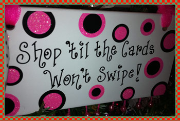 Large white sign with black and pink polka dots, says 'Shop til the cards won't swipe'