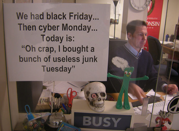man works on computer behind window that has a sign saying-Today is...I bought a bunch of useless junk Tuesday.