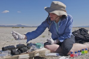 Young woman in sun hat sitting on ground in desert setting sticking syringe in rock-like mud samples