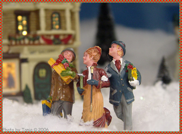 Ceramic man with gifts in arms and a woman and man arm-in-arm, all in old-fashioned clothes and walking together