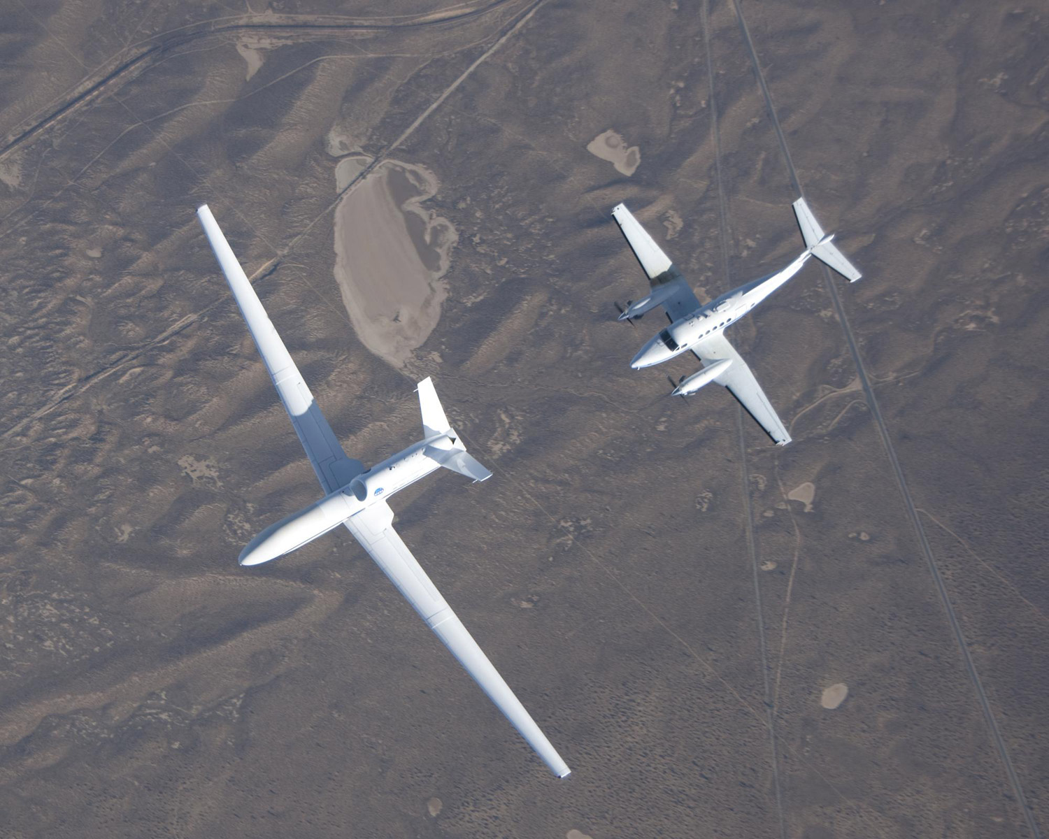 Overhead view of two planes flying; front plane has large wingspan, back plane is smaller with propellers