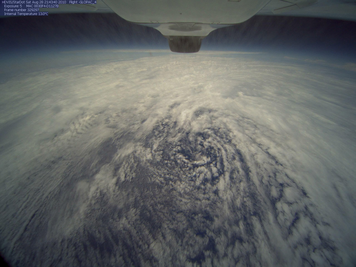 Aerial view of expansive cloud system, swirling in the center; underbelly of back of plane at top of frame
