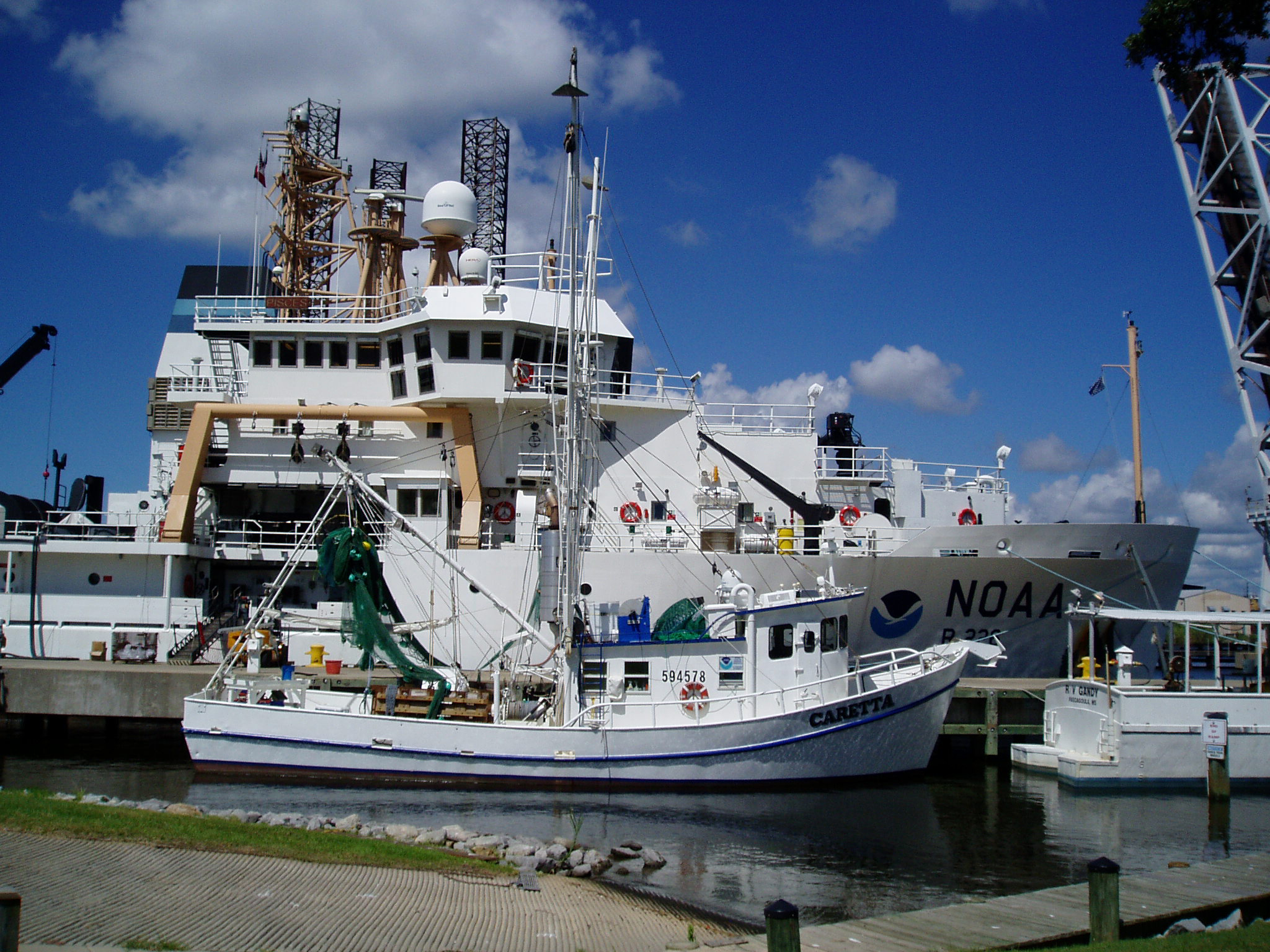 Large multi-level ship, top festooned with scientific instruments, at dock; with a smaller boat docked alongside.