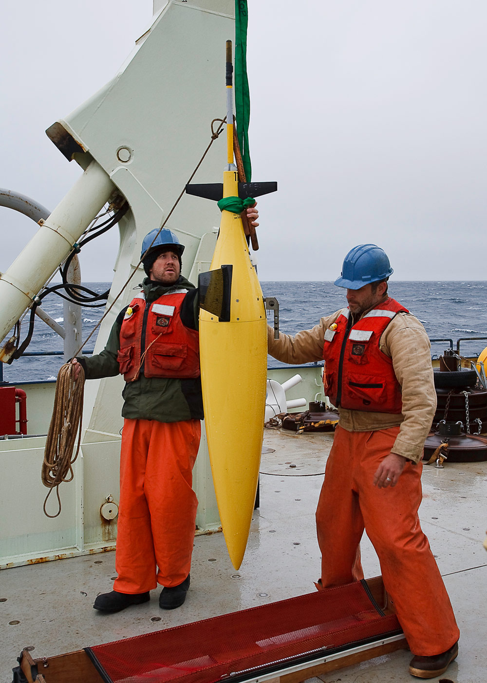 Two men in orange uniforms on boat deck guiding a hanging yellow torpedo-like instrument out of its case