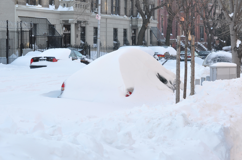 Residential city street blanketed in couple feet of snow, car in foreground completely covered in snow