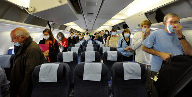 Inside airplane cabin, dozens of people walk down isles wearing surgical masks.