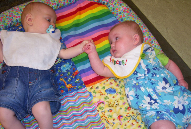 Two babies lay on their backs on a colorful blanket looking at each other, arms outstretched and fists touching