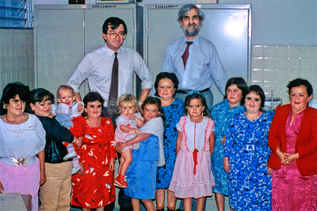 Two adult men stand behind a row of 11 women and two children, who come up to men's waist in height