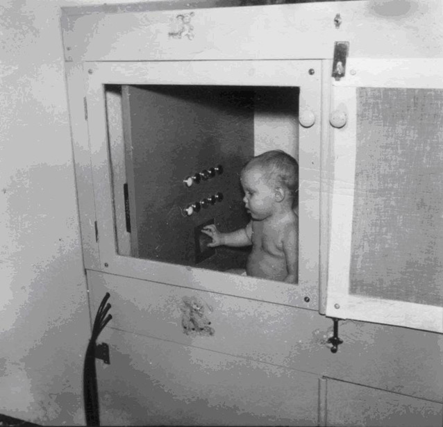 Baby in large box with large front window, panel with two rows of buttons and small square hole on one wall