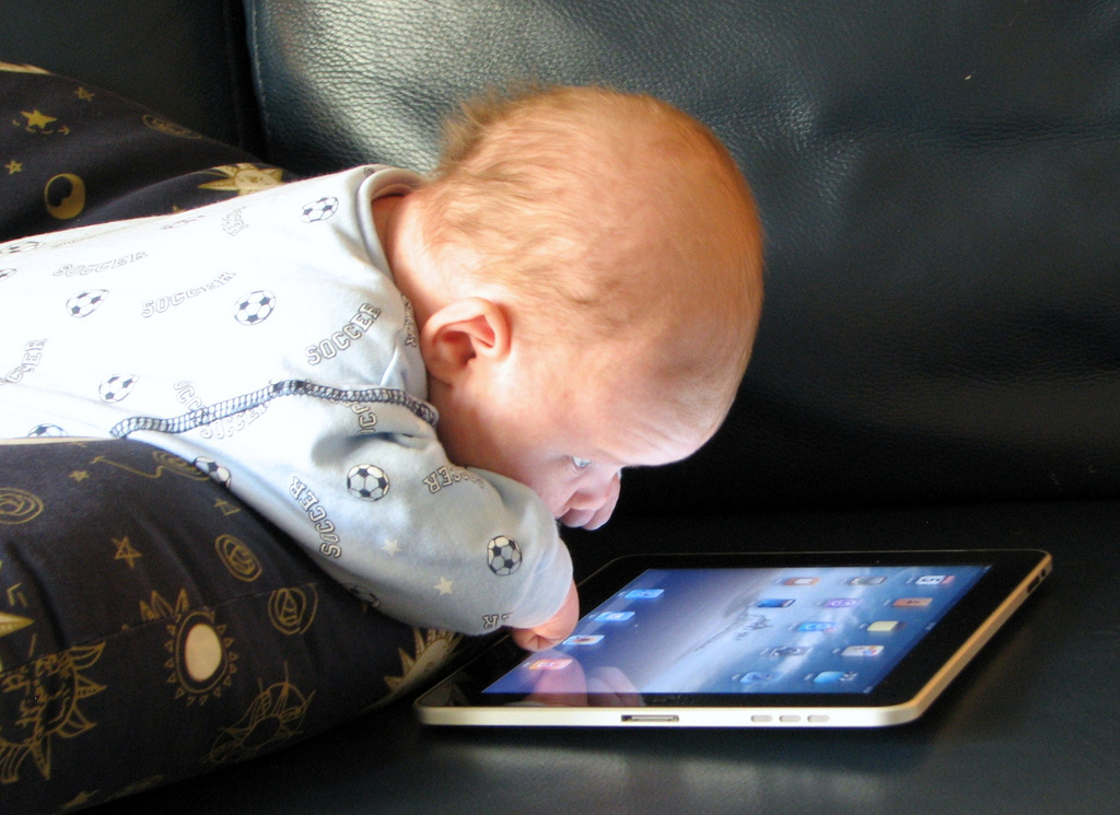 Very young baby lying on stomach on pillow staring at an iPad screen